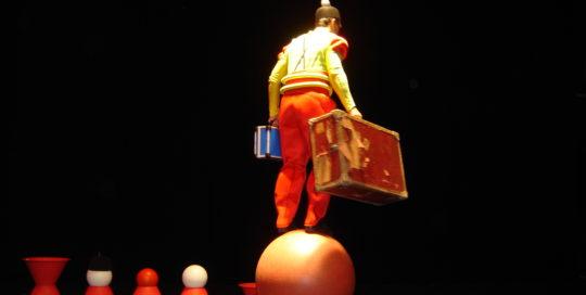 Un clown avec deux valises qui part en équilibre sur une boule Cirkonflex