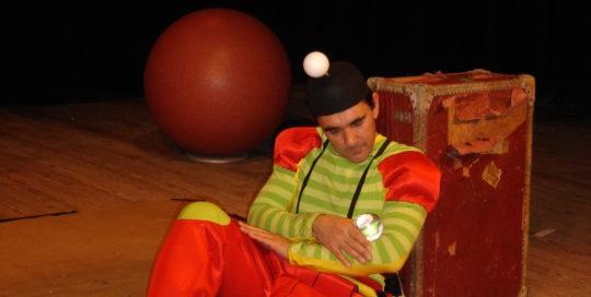Un jongleur assis et adossé à une valise berce une balle bulle Cirkonflex