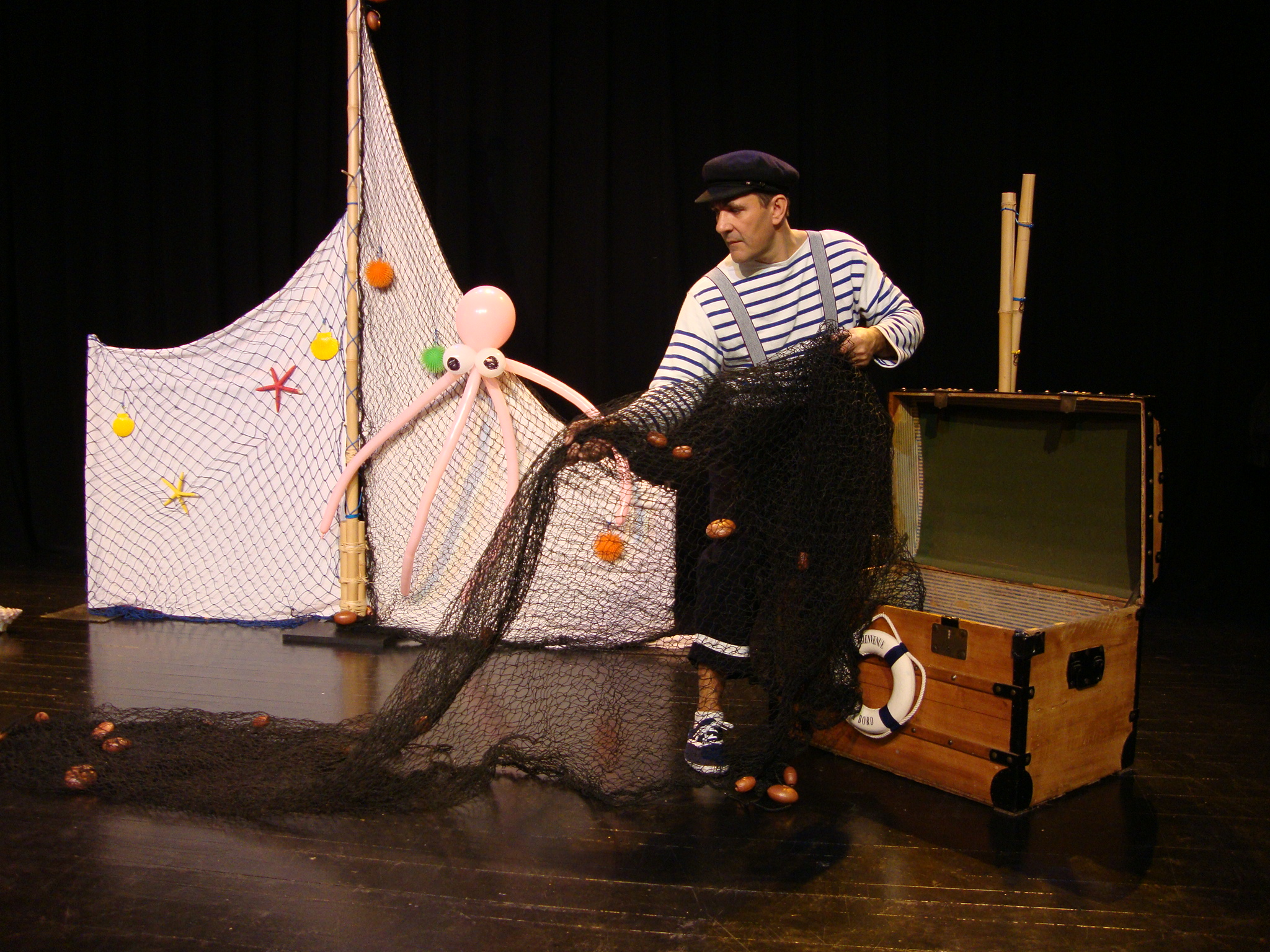 Marin qui range son filet de pêche dans un coffre de pirate. Cirkonflex
